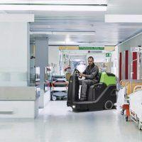 Flur im Krankenhaus mit unscharfem Arzt in Bewegung und Lift rot und Bett
